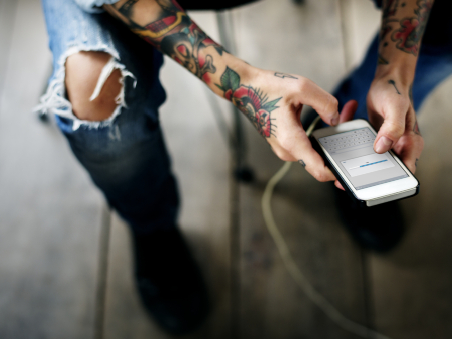 Tattooed Person Using Their Mobile Phone