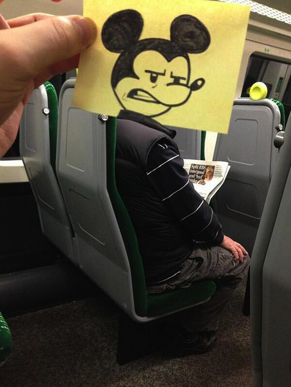 Clever sketch of an angry looking Mickey Mouse head reimposed on an unsuspecting commuter