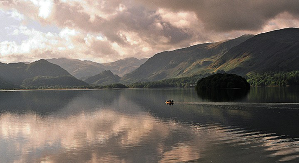 Stunning photographic image of a stormy lake and valley backdrop with a tiny boat on the otherwise still, calm water