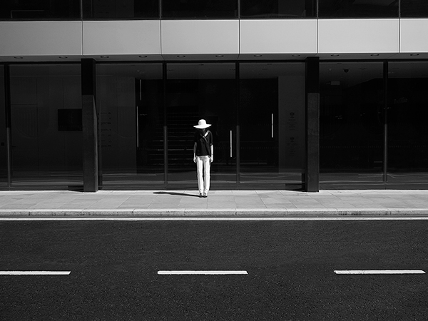 Landscape black and white photograph of a woman across the street wearing a white hate, black blouses and white trousers facing the camera. She is standing in front of a black and white concrete building