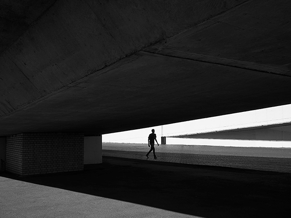 Black and white, light and shadow photograph taken at a striking angle showing the sky lit up all white, a thin man walking slightly taller than the photographer in the background and a big concrete slab overhead which could be a road bridge