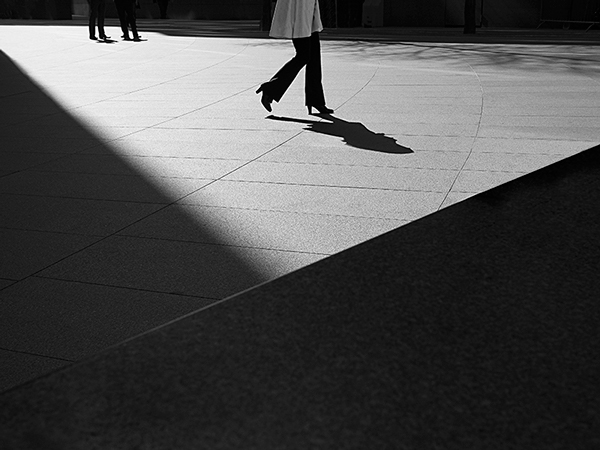 Striking photograph using a black and white shot  of a woman walking on a vast. concrete slab path wearing heeled boots