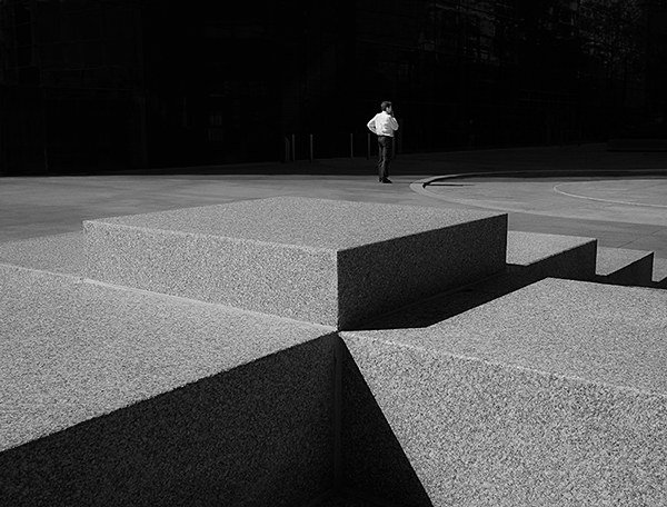 Black and white photograph using light and dark shadowing shows a man in the distance wearing a white shirt and black trousers. The angle is over a few concrete blocks with striking lines created by the shadow