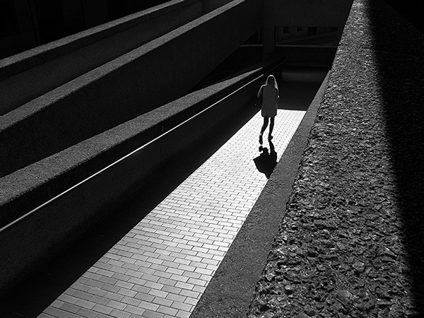Black and white photograph with light and shadow effect - shows a woman walking down a sloping brick path that is lit up by sunshine and surrounded by strong, black concrete walls crisscrossing above her.