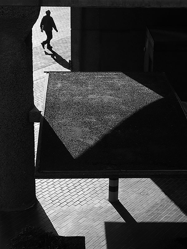 Light and shadow photograph with abstract angles. Shows a man walking seemingly away from the camera on a bright path outside and taken from a slightly confusing inside place with multiple layers